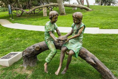 Bronze Sculpture of Two Children Sitting on a Log